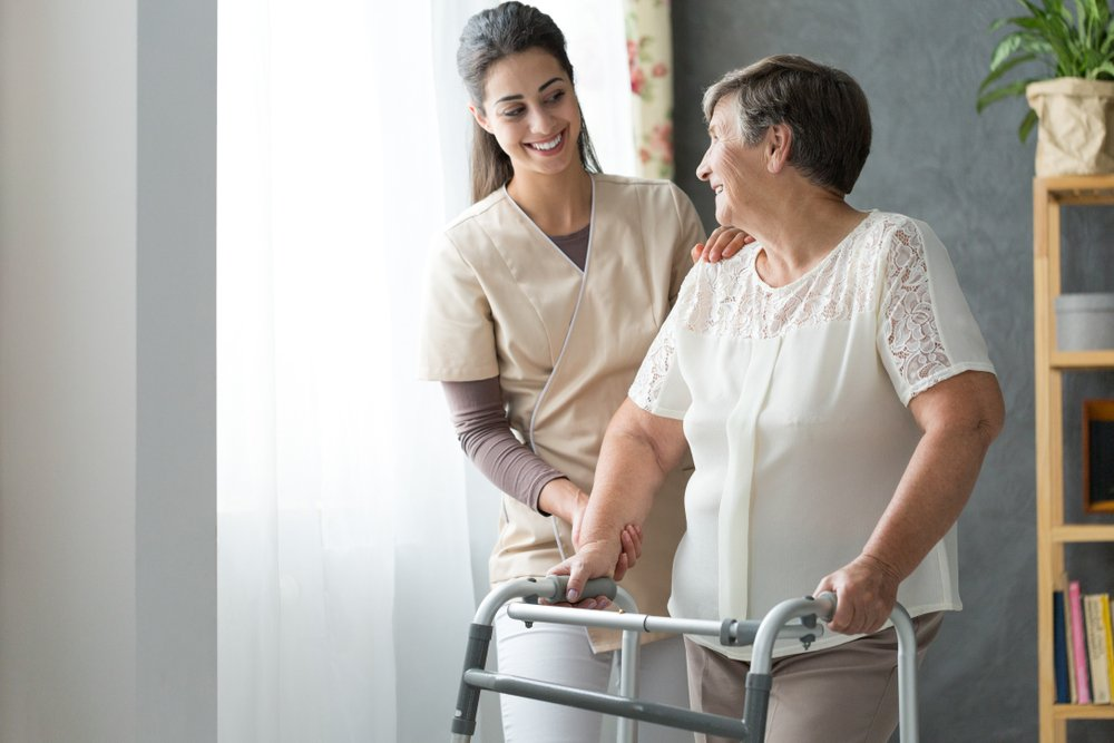 A photo of beautiful caregiver helping an old lady at a nursing home. | Photo: Shutterstock.
