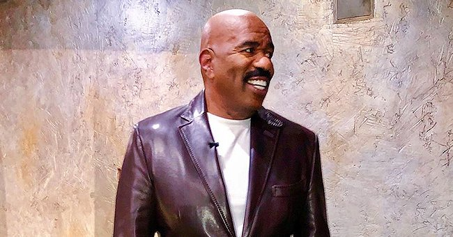 Steve Harvey Flashes a White Smile While Wearing a Leather Jacket & Matching Olive Trousers