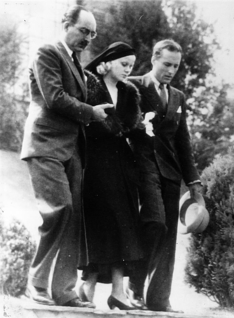 American film actress Jean Harlow being assisted from her house by her step-father Mario Bello and a relative Donald Robertson on her way to the funeral of her husband Paul Bern, who was found shot dead at his Beverly Hills home. | Source: Getty Images