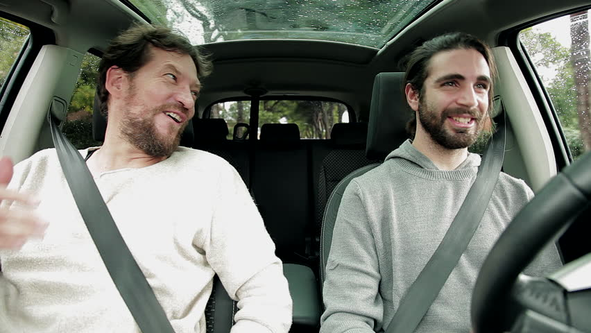 Two male drivers talking and laughing in a car while driving | Source: Shutterstock