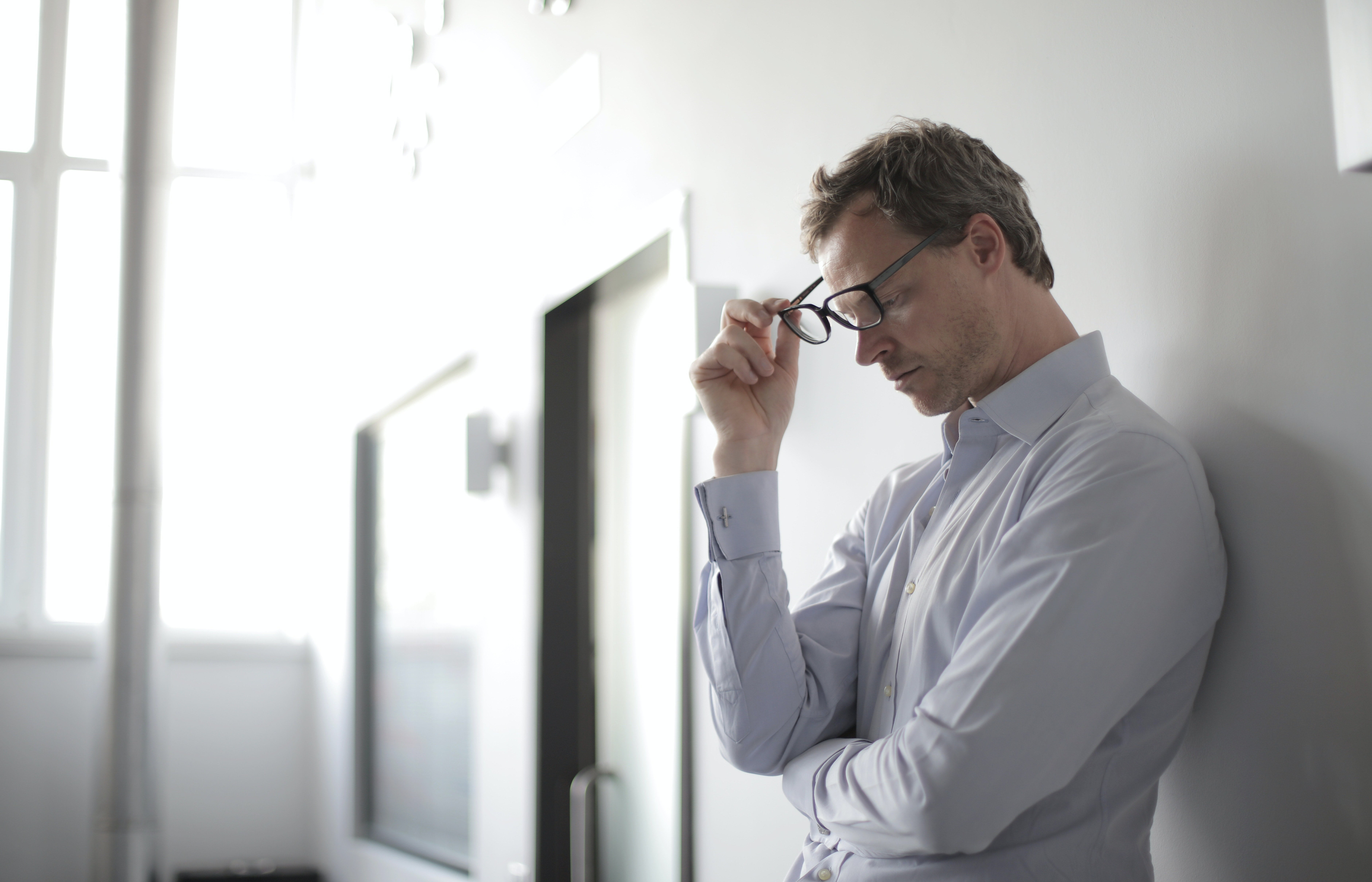 A man holding on to his glasses while looking down and leaning against a wall.   Photo: Pexels