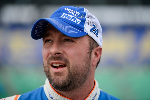Eric McClure, driver of the #24 Reynolds Wrap Toyota, stands in the garage area during qualifying for the NASCAR XFINITY Series Kansas Lottery 300 on October 17, 2015 | Photo: Getty Images