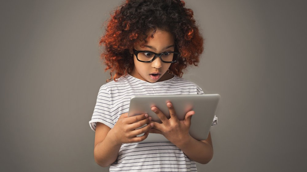 Shocked young girl views something on a tablet | Photo: Shutterstock