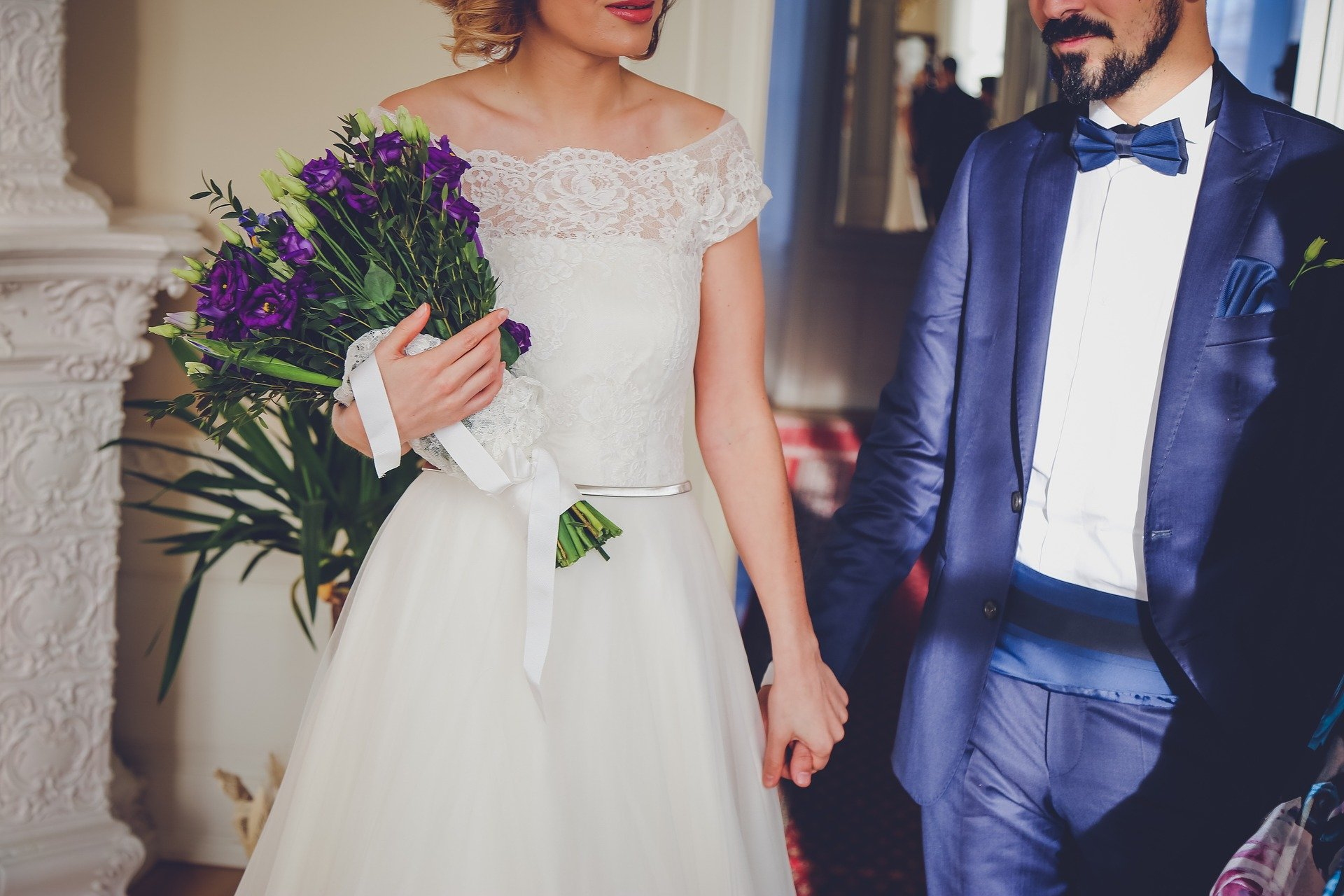 A couple in formal wear with the wife holding a bouquet of flowers as they hold hands   Photo: Pixabay/StockSnap