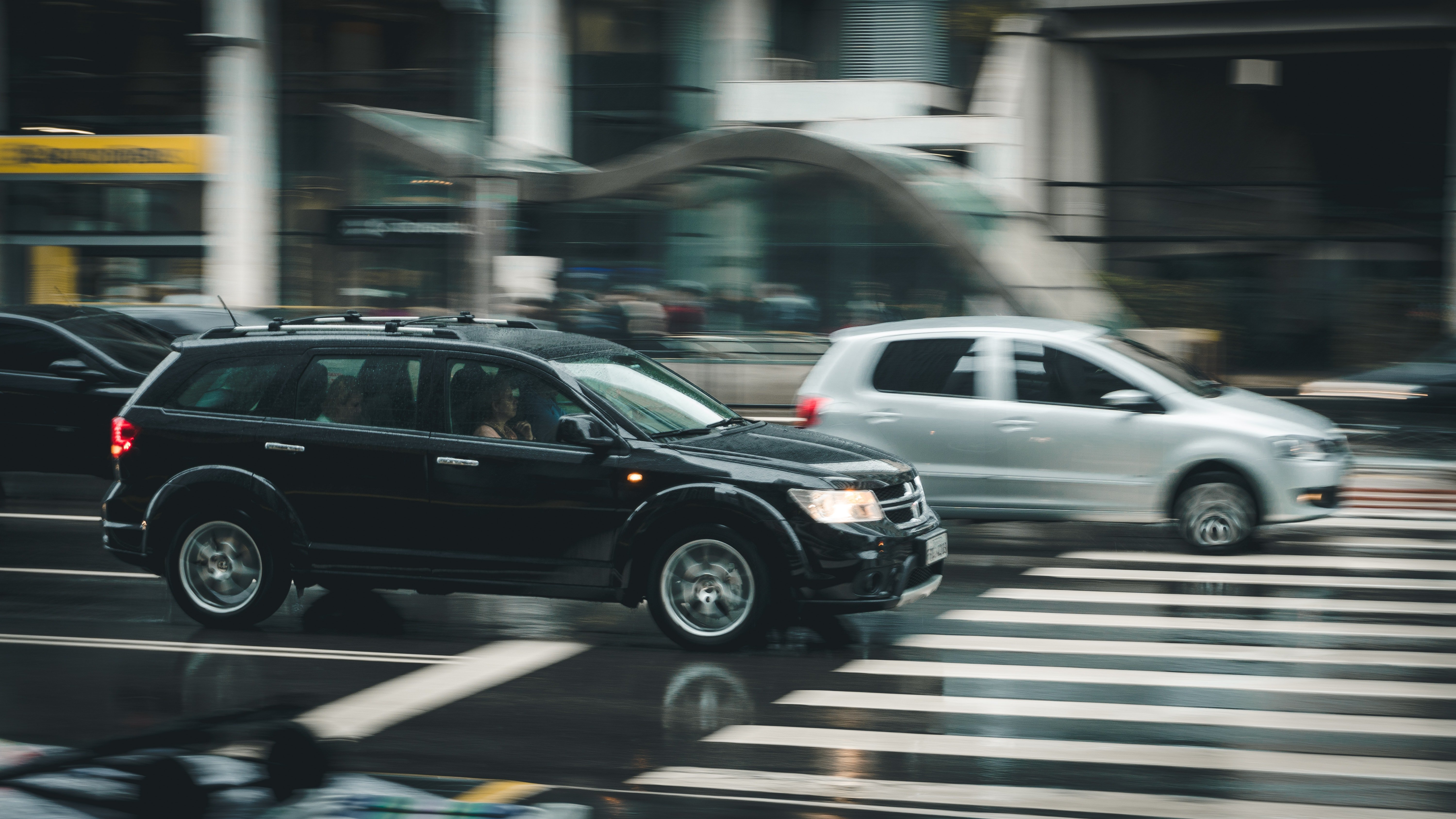 Two cars driving over a zebra stripe.   Source: Pexels/Kaique Rocha