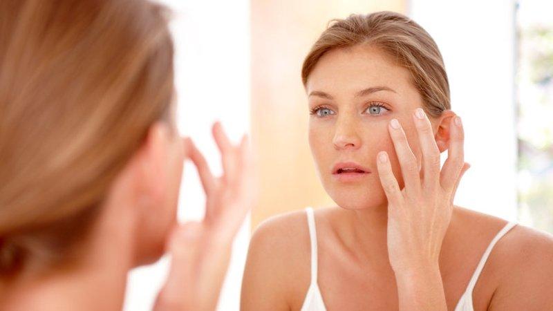 Mujer revisando su piel en el espejo. | Imagen: GoodFreePhotos
