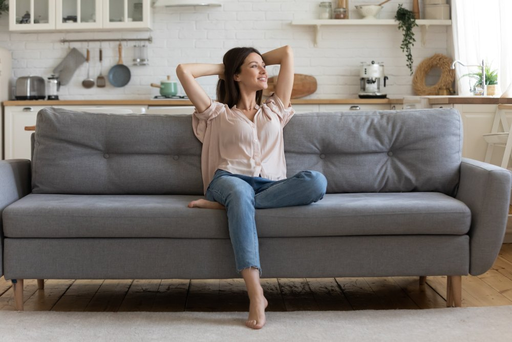 A relieved and happy young woman sitting in a cozy living room with herhands behind her head   Photo: Shutterstock/fizkes