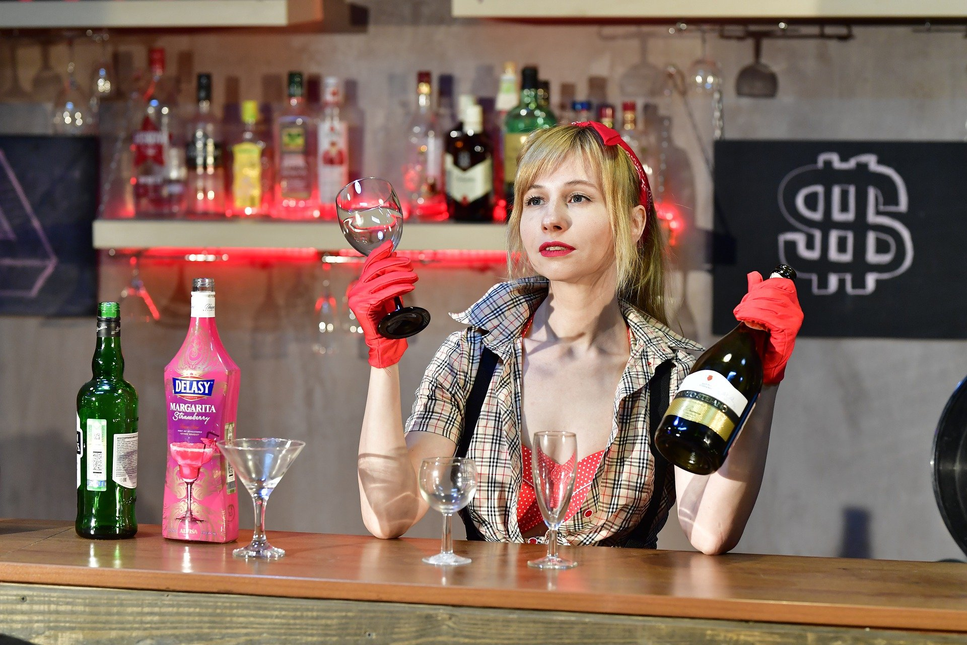 A barmaid holding up and offering drinks to a patron   Photo: Pixabay