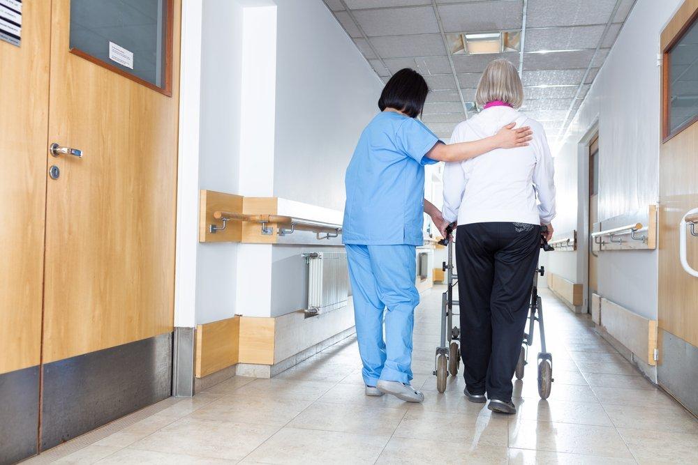 Une infirmière aide une pensionnée à marcher dans les couloirs d'une maison de retraite.   Shutterstock