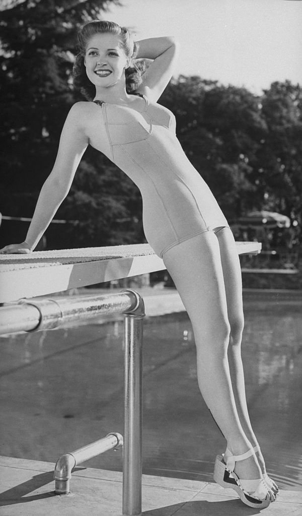 A portrait of Anne Gwynne wearing bathing suit and sandals and posing by a swimming pool diving board circa 1938. | Photo: Getty Images
