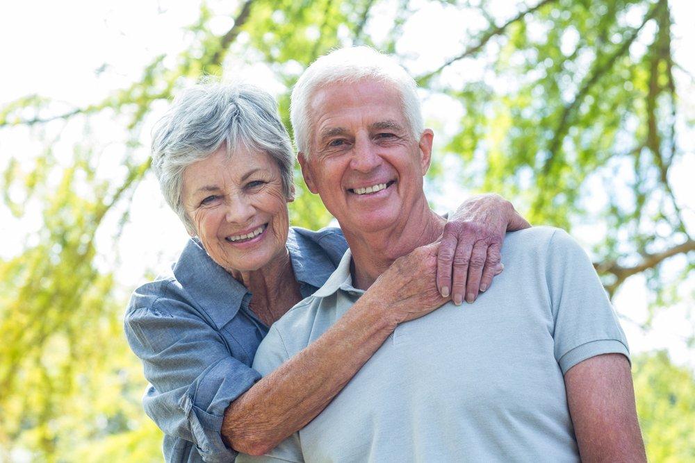 Un couple de personnes âgées souriant dans un parc. l Source: Shutterstock