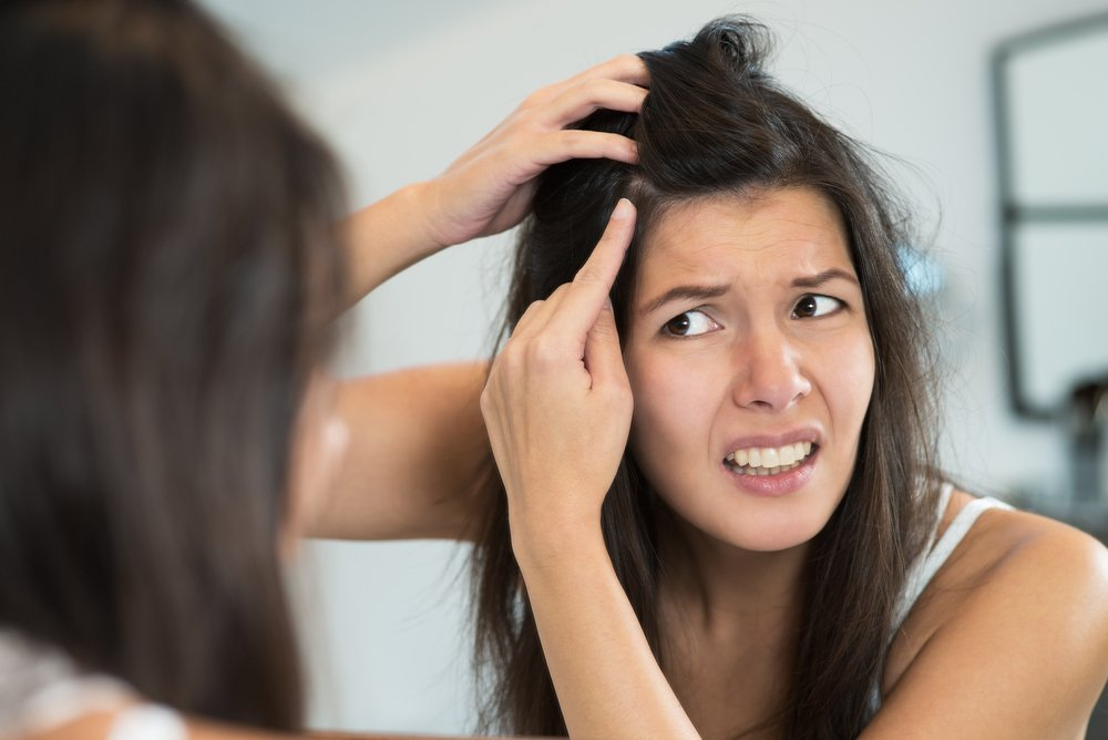 Young woman looking in the bathroom mirror at her scalp.   Source: Shutterstock