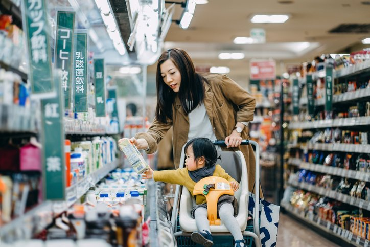 Cute little daughter sitting in a shopping cart grocery shopping for dairy product with young Asian mother in a supermarket | Photo: Getty Images