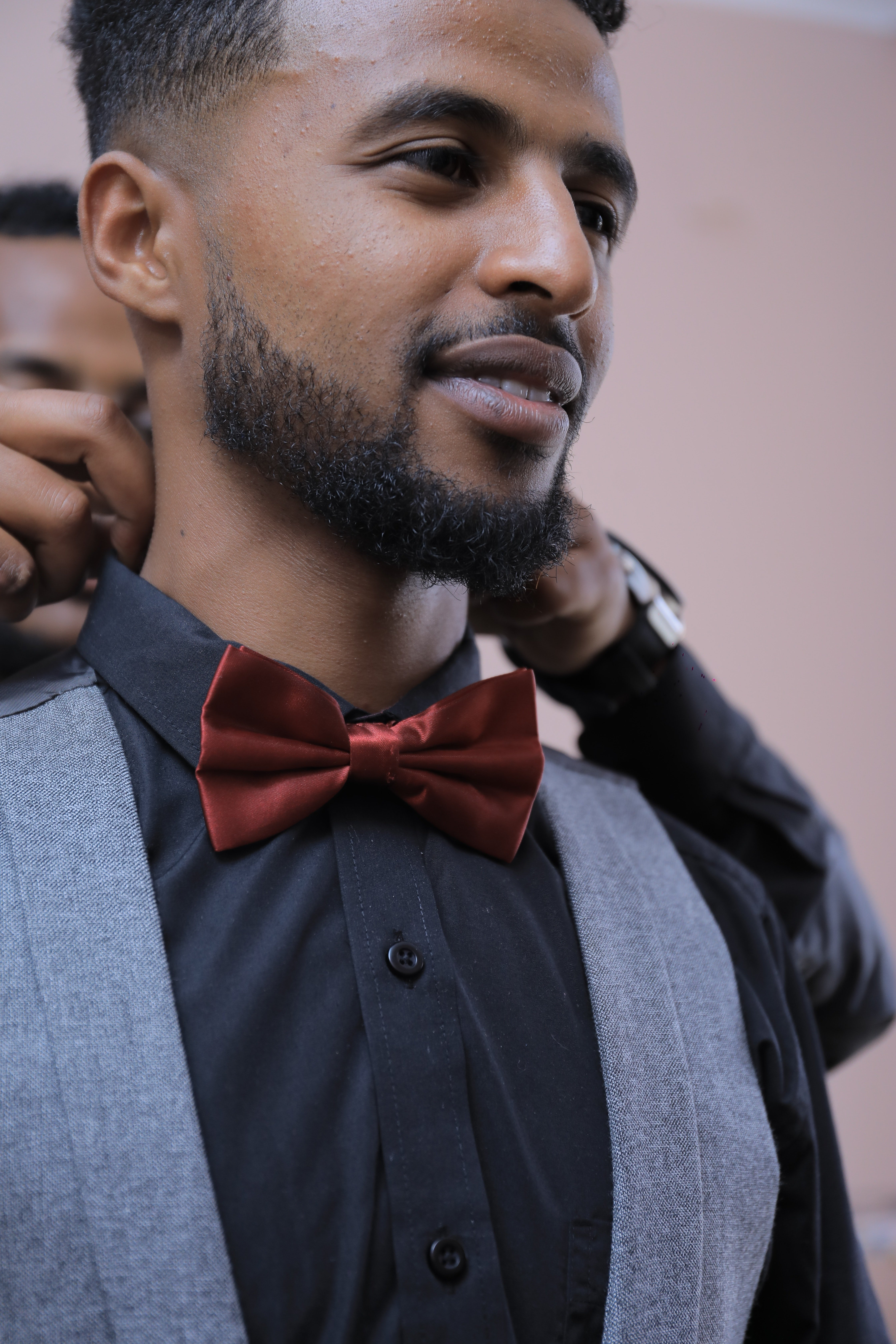 The stranger helped the man tie his bow tie.   Photo: Pexels