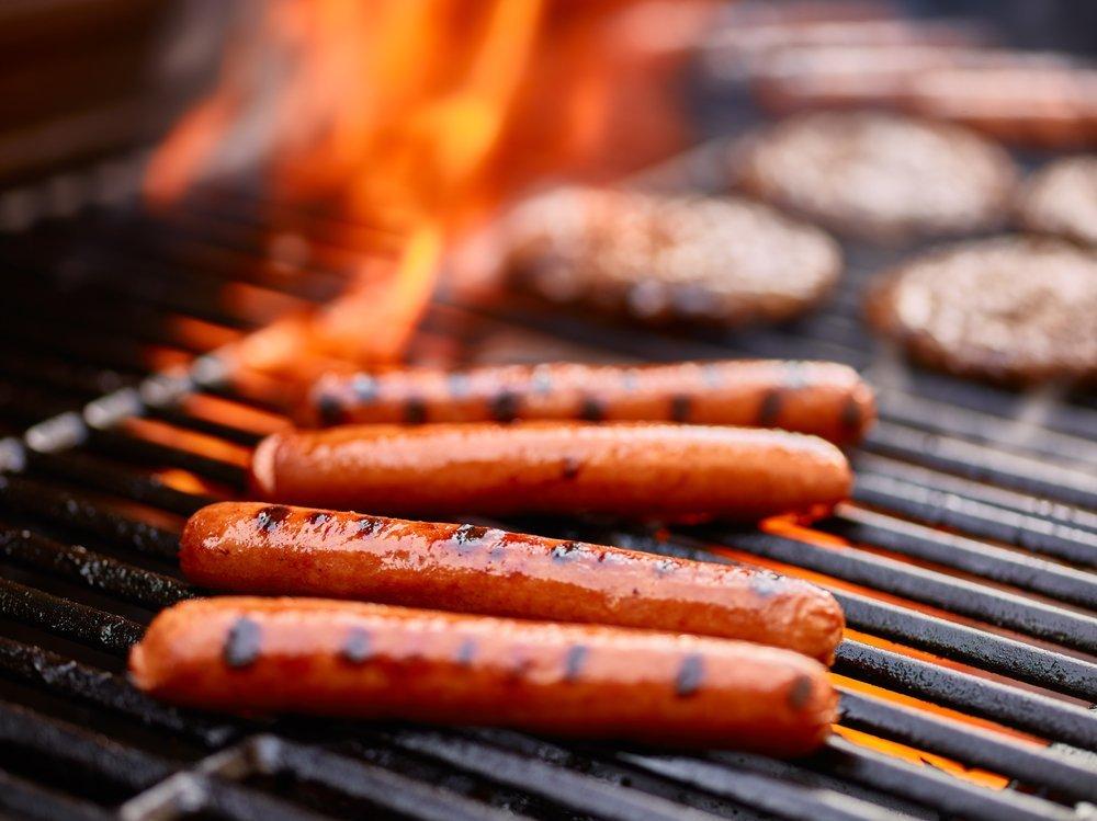 Fot dogs savoureux en train de cuire sur un grill avec des hamburgers. | Shutterstock