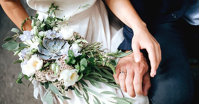A bride and groom about to hold hands on their wedding day   Photo: Shutterstock