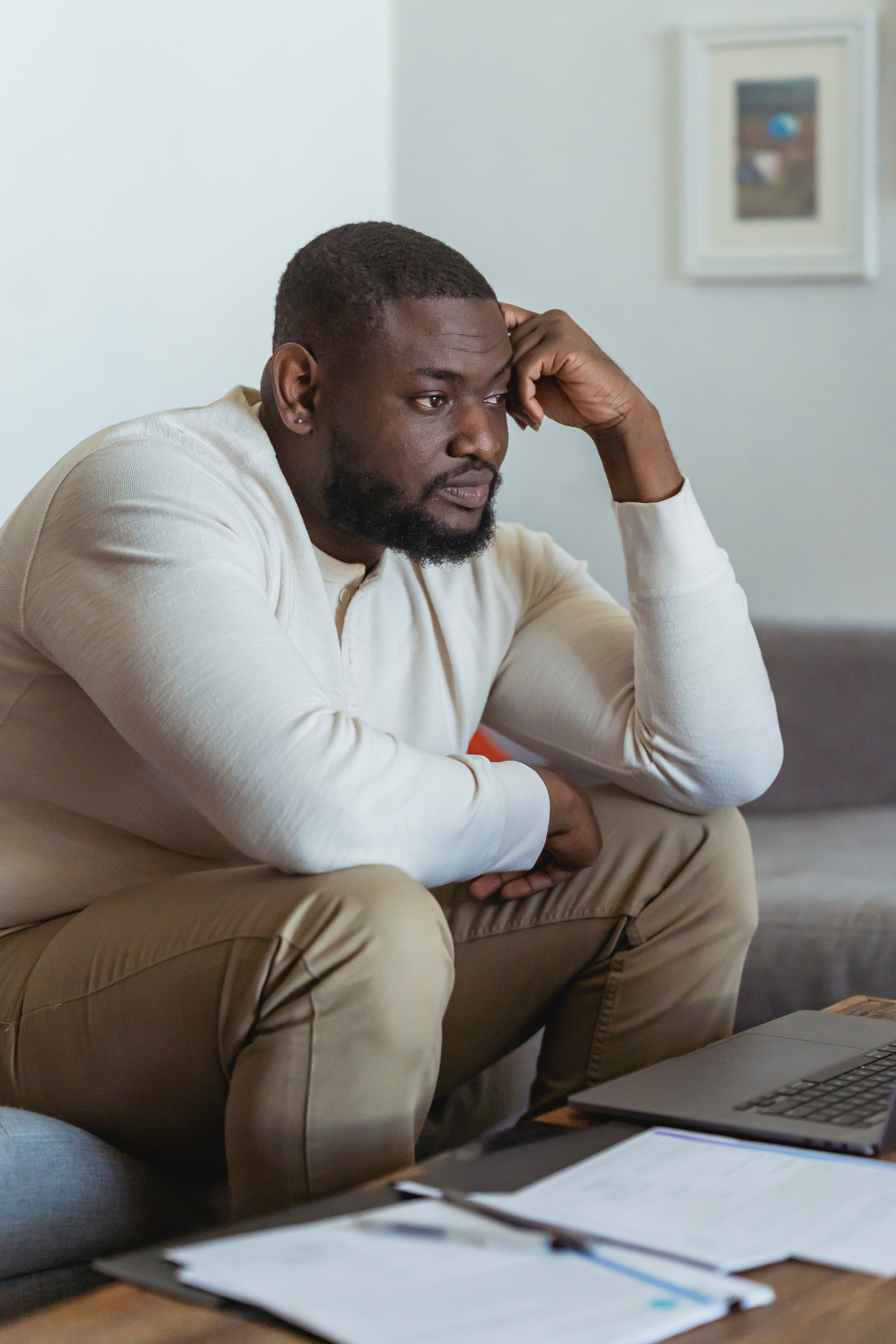 Frustrated black man sitting near laptop and thinking   Photo: Pexels