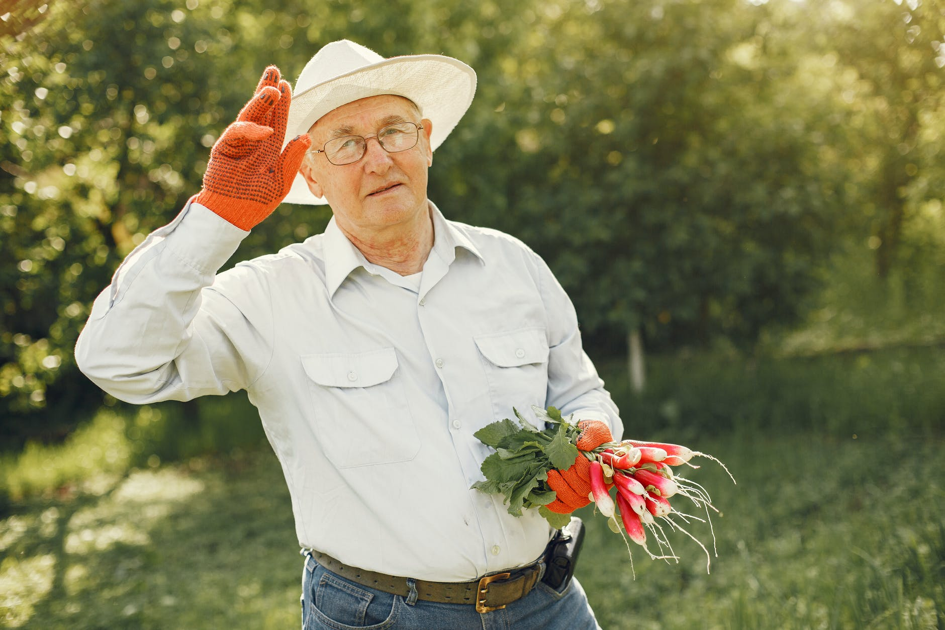 Man in gardening clothes with a handful of radishes | Source: Pexels