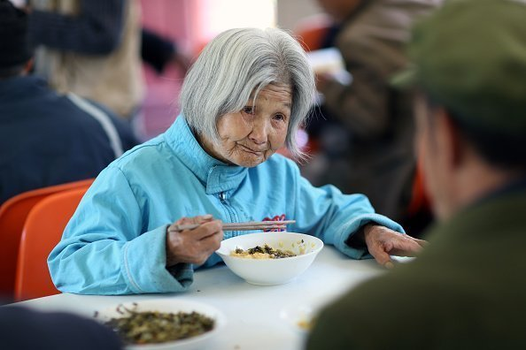 98-year-old lady eating breakfast at a nursing home in Zhenping County | Photo: Getty Images