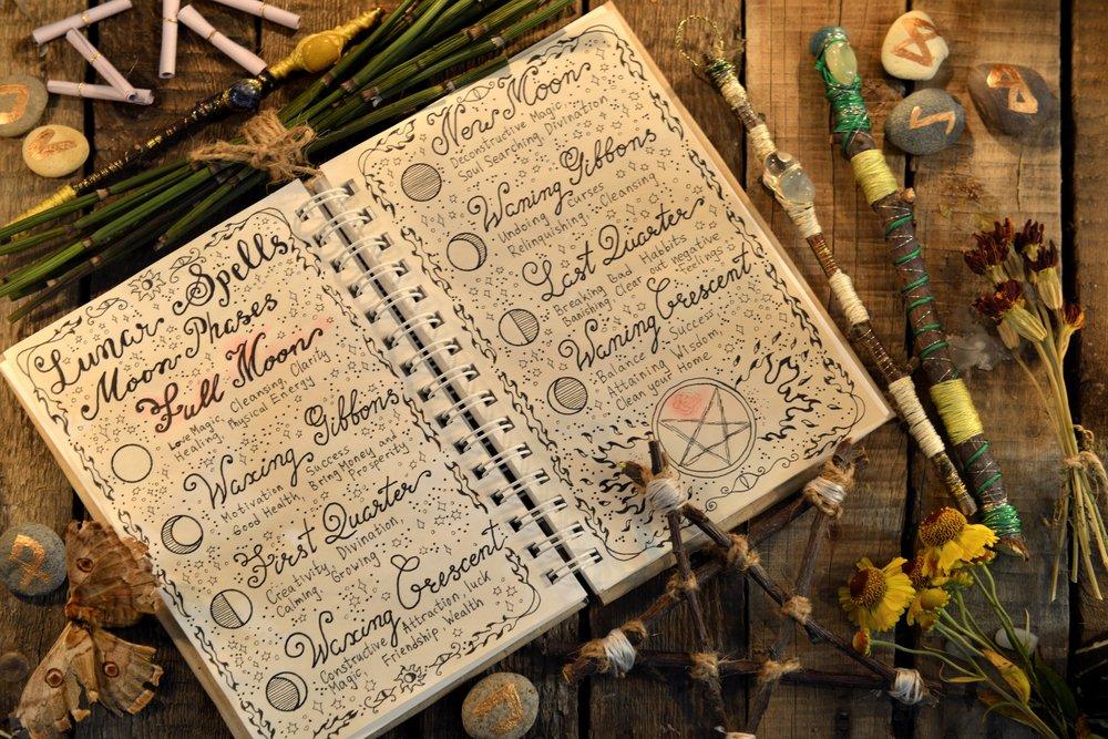 Diario con hechizos lunares, pentagramas y varitas mágicas en una mesa. Shutterstock