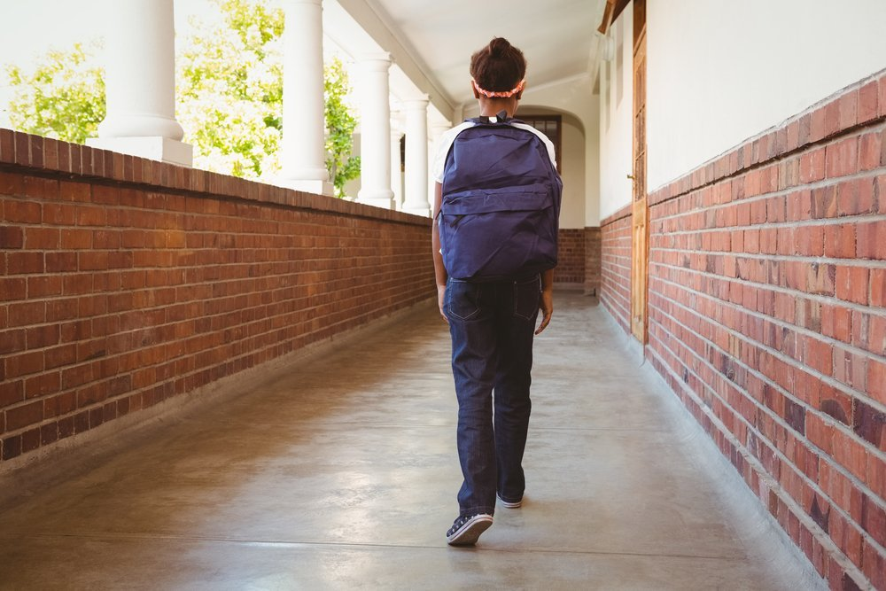 Girl walking in school corridor. | Source: Shutterstock