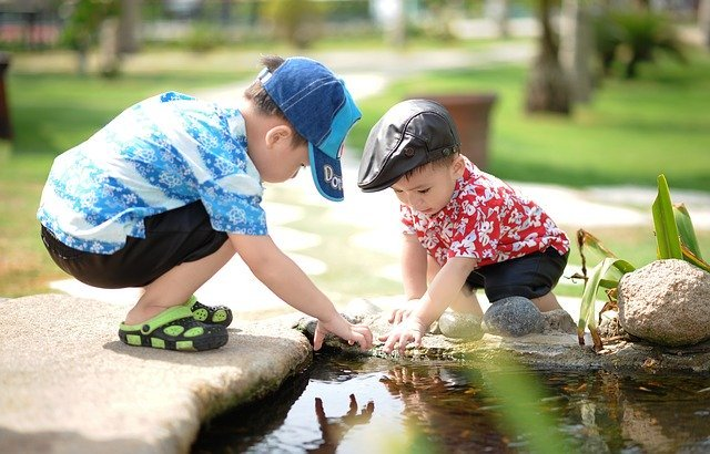 Two boys play near a pond | Photo: Pixabay
