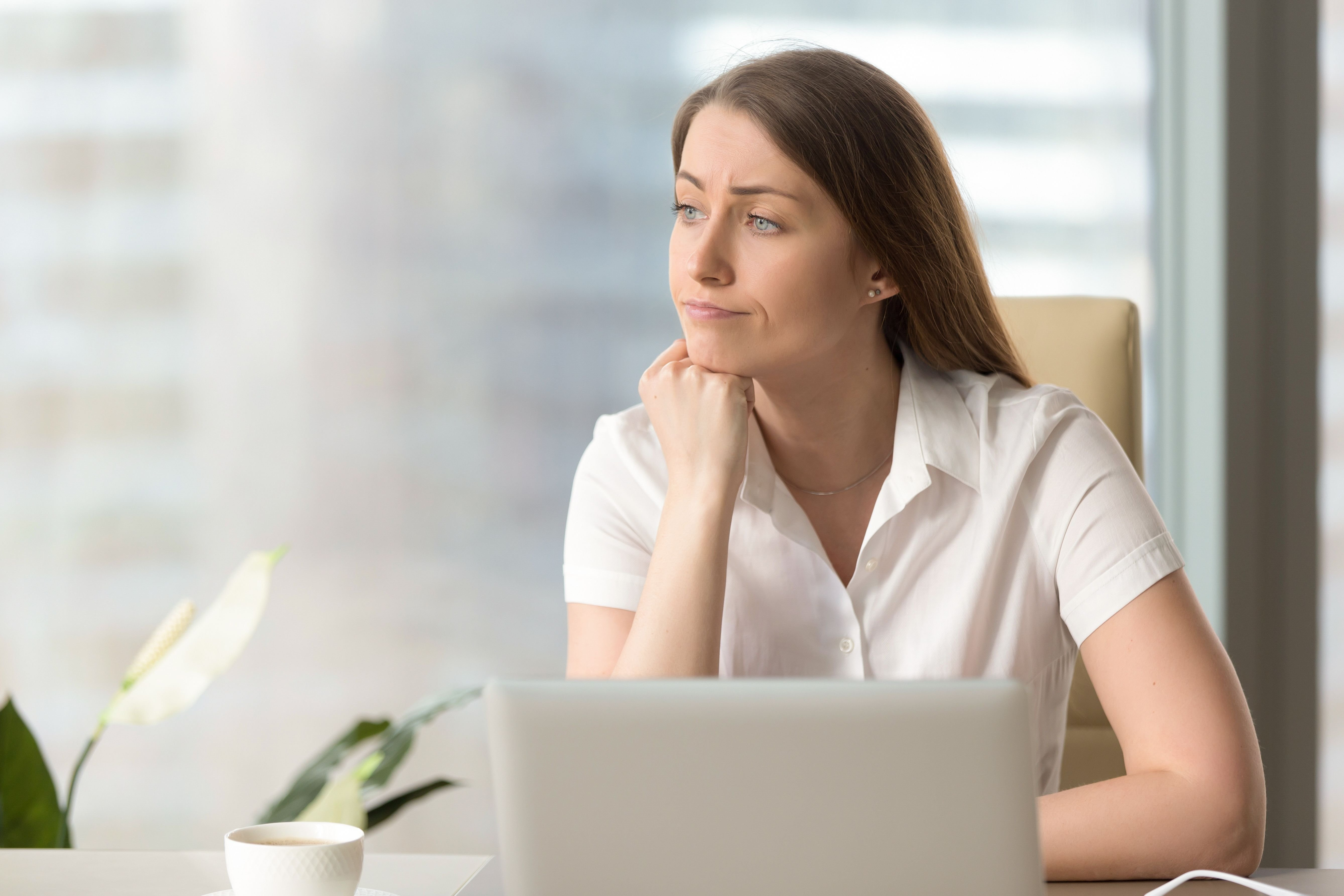 A woman looking out the window while working on her laptop. | Source: Shutterstock