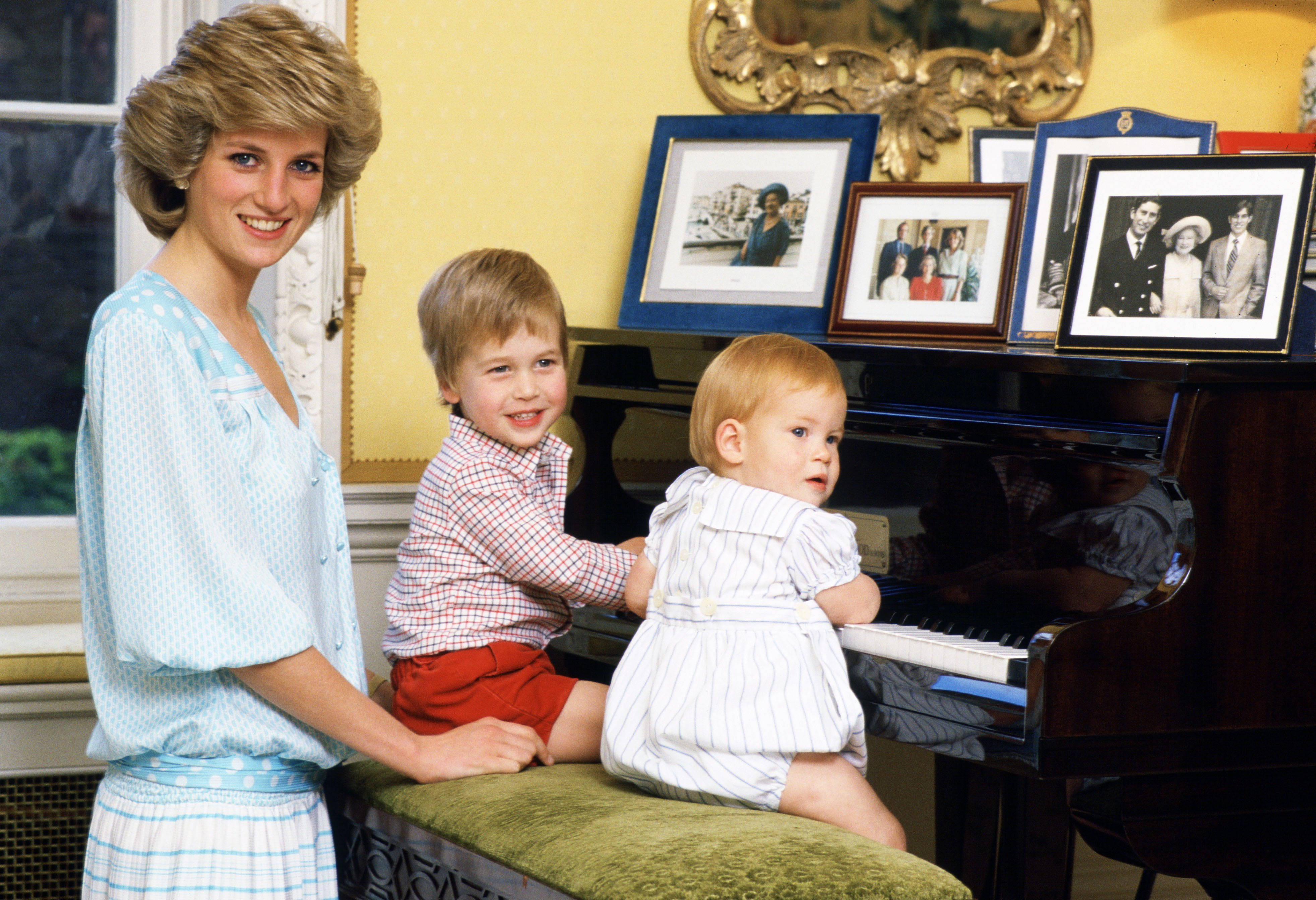 Diana, Princess of Wales with her sons, Prince William and Prince Harry, at the piano in Kensington Palace | Getty Images