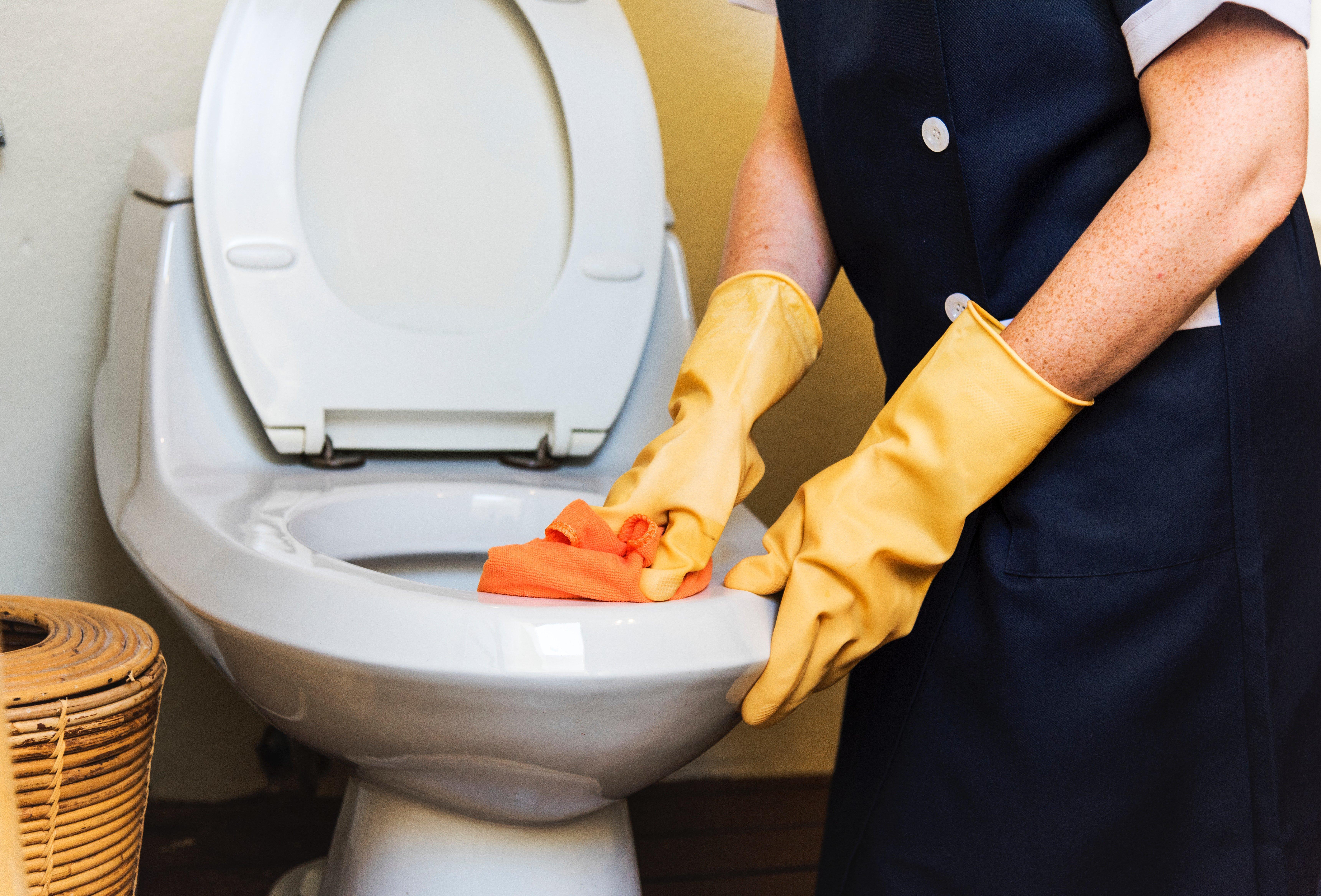 Un homme en train de nettoyer  la cuvette de toilette. | Photo : Pexels