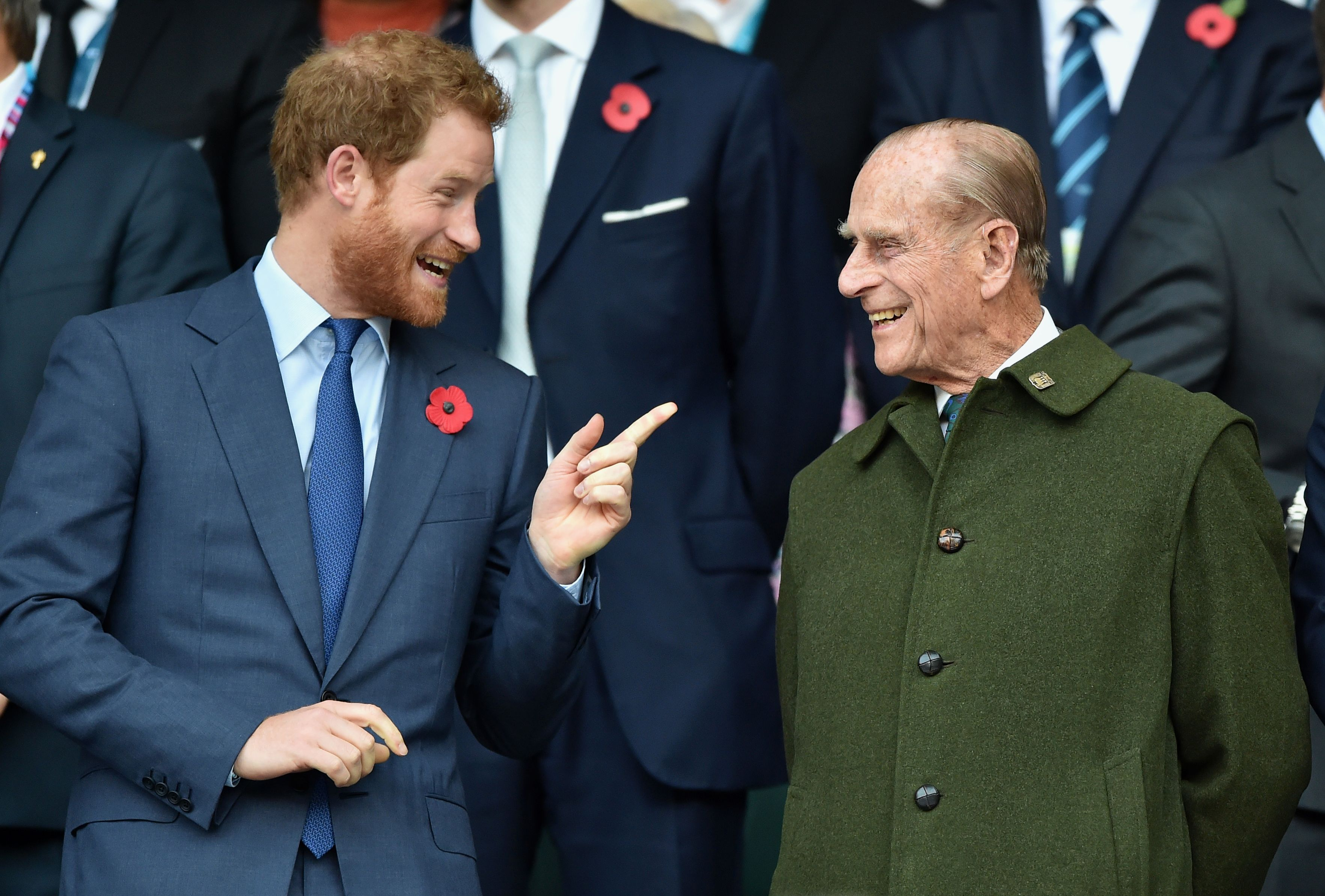 Prince Harry and Prince Philip, Duke of Edinburgh chatting at the 2015 Rugby World Cup Final match between New Zealand and Australia at Twickenham Stadium in London, England | Photo: Getty Images