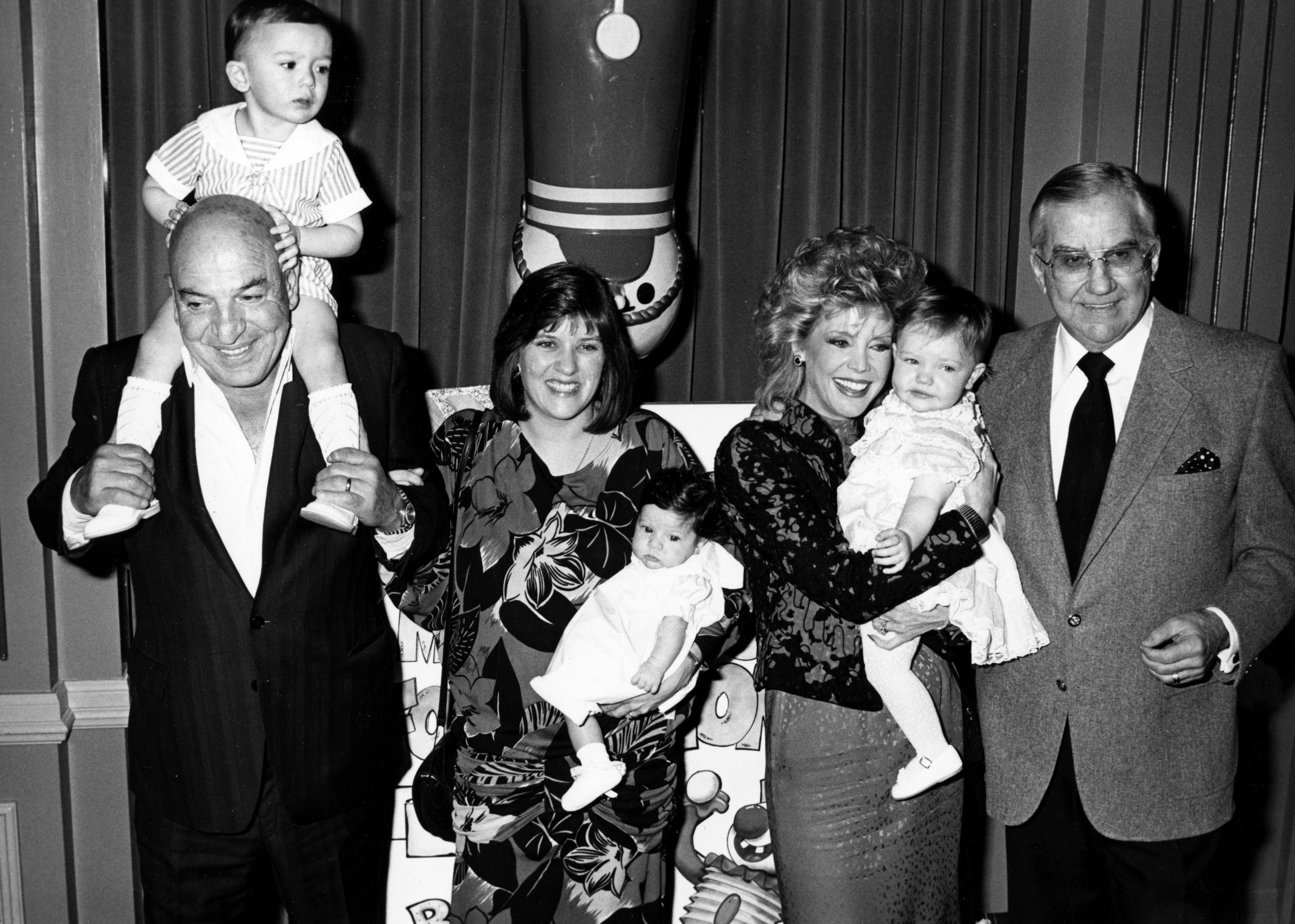 Telly Savalas, wife Julie Hovland, son Christian Savalas and daughter Ariana Savalas and Ed McMahon, wife Victoria McMahon and daughter Katherine McMahon attend Young Musicians Foundation Celebrity Mother-Daughter Fashion Show on March 26, 1987 | Photo: Getty Images