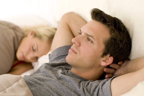 A worried man next to his sleeping wife in bed. | Source: Shutterstock.