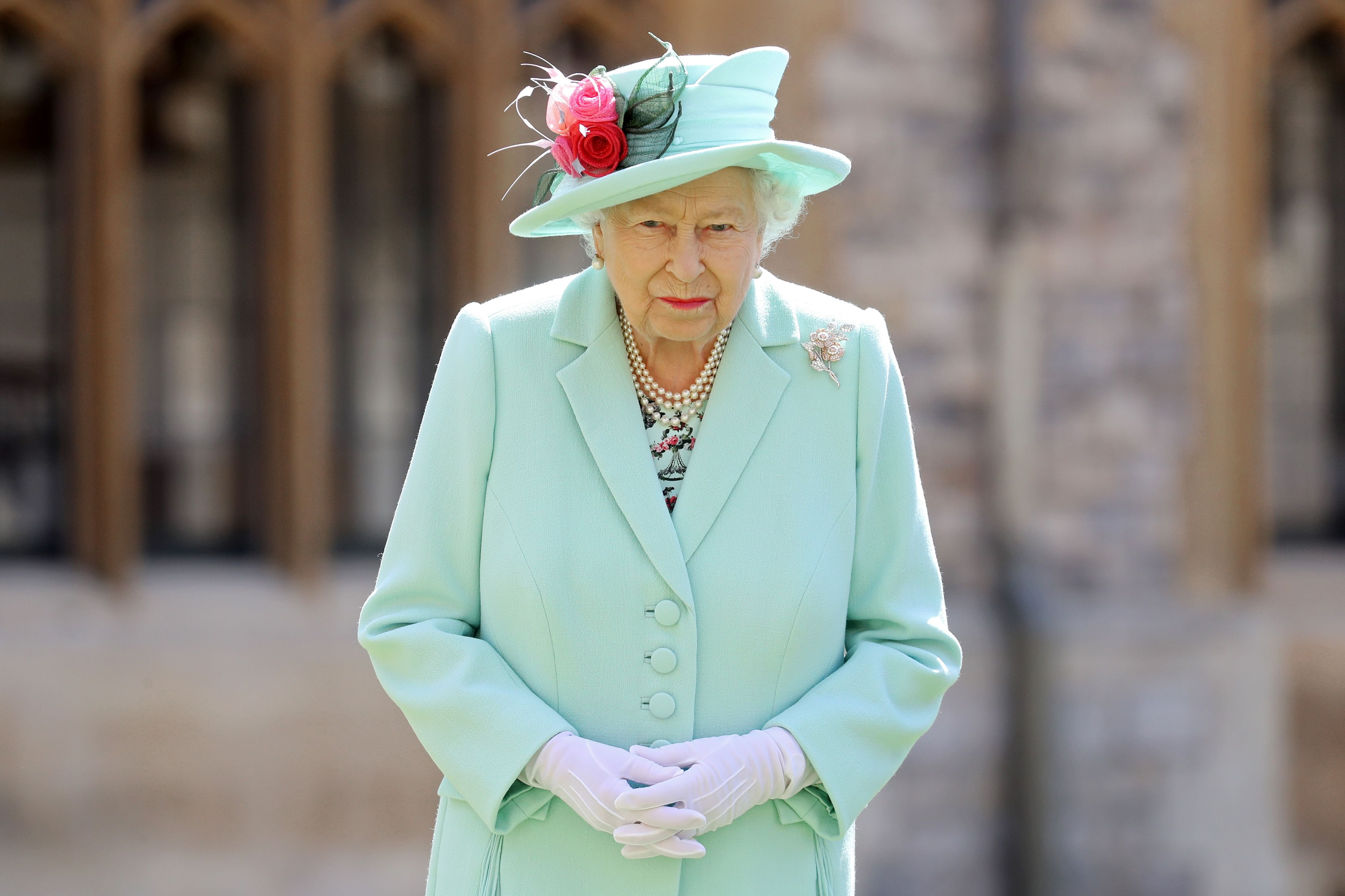 Queen Elizabeth II posed after awarding Captain Sir Thomas Moore with the insignia of Knight Bachelor at Windsor Castle on July 17, 2020 | Photo: Getty Images
