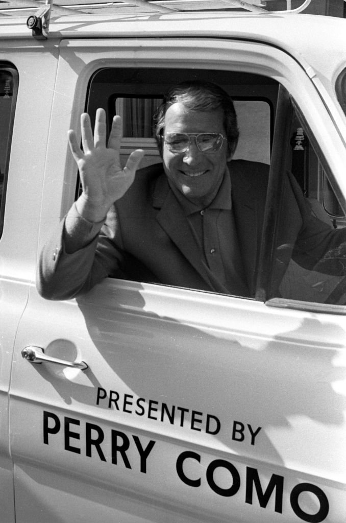 "American singer Perry Como (1912 - 2001) in a van on the door of which is written ""Presented by Perry Como"" 