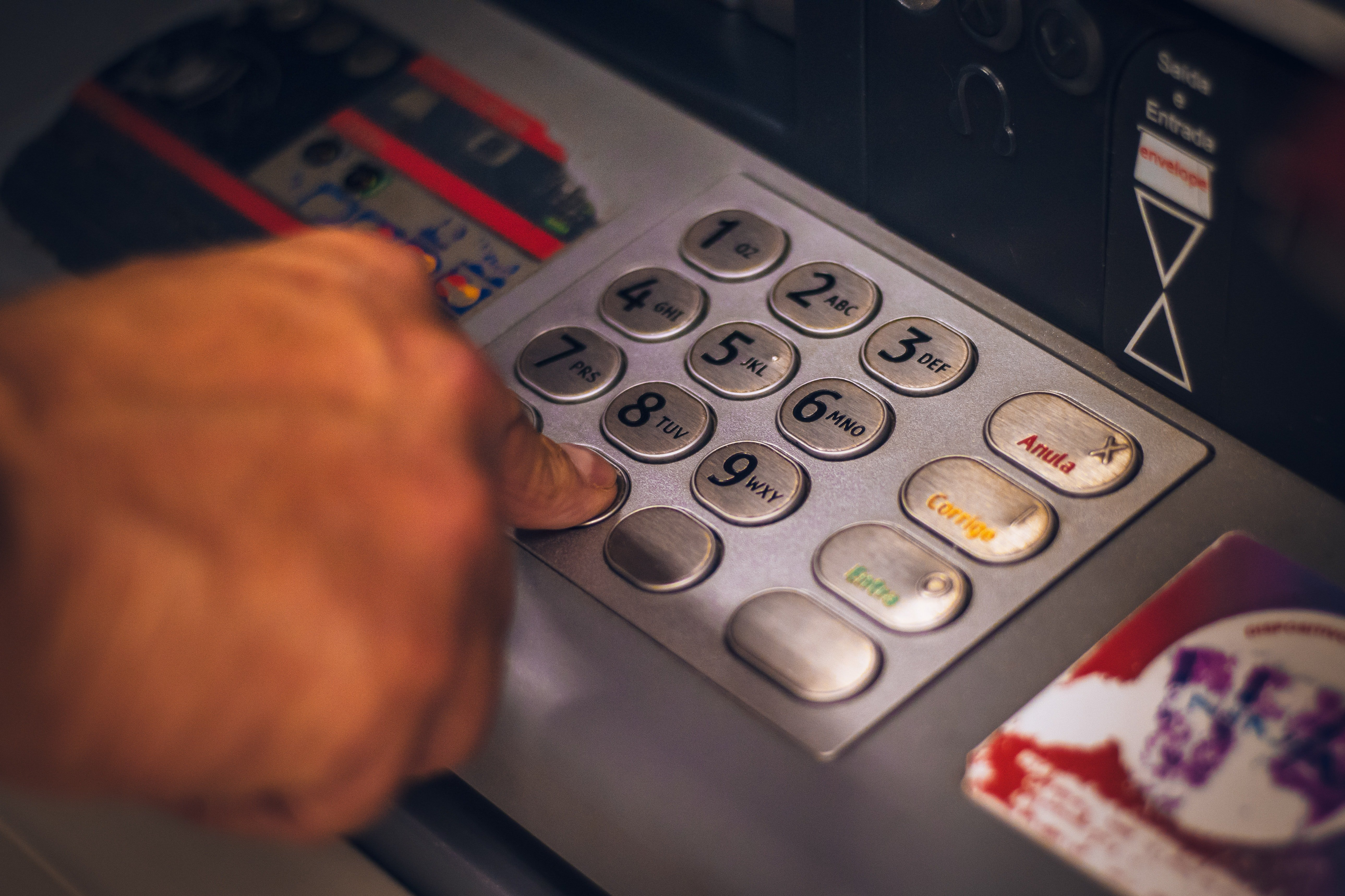 A customer withdrawing money at an ATM   Source: Pexels