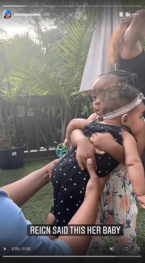 A screenshot from a clip of Toya Johnson's 3-year-old daughter Reign holding Zonnique Pullins' child, Hunter Zoelle James | Photo: Instagram.com/zonniquejailee