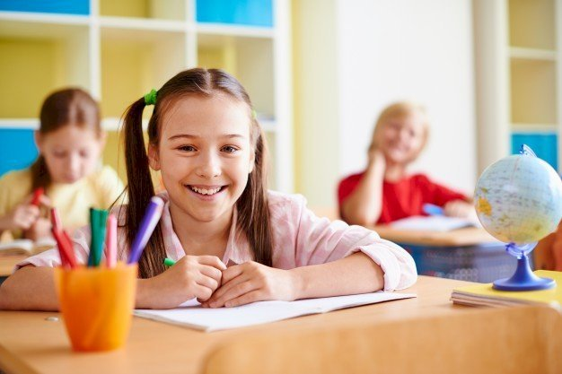 A girl smiling in a classroom | Source: Freepik