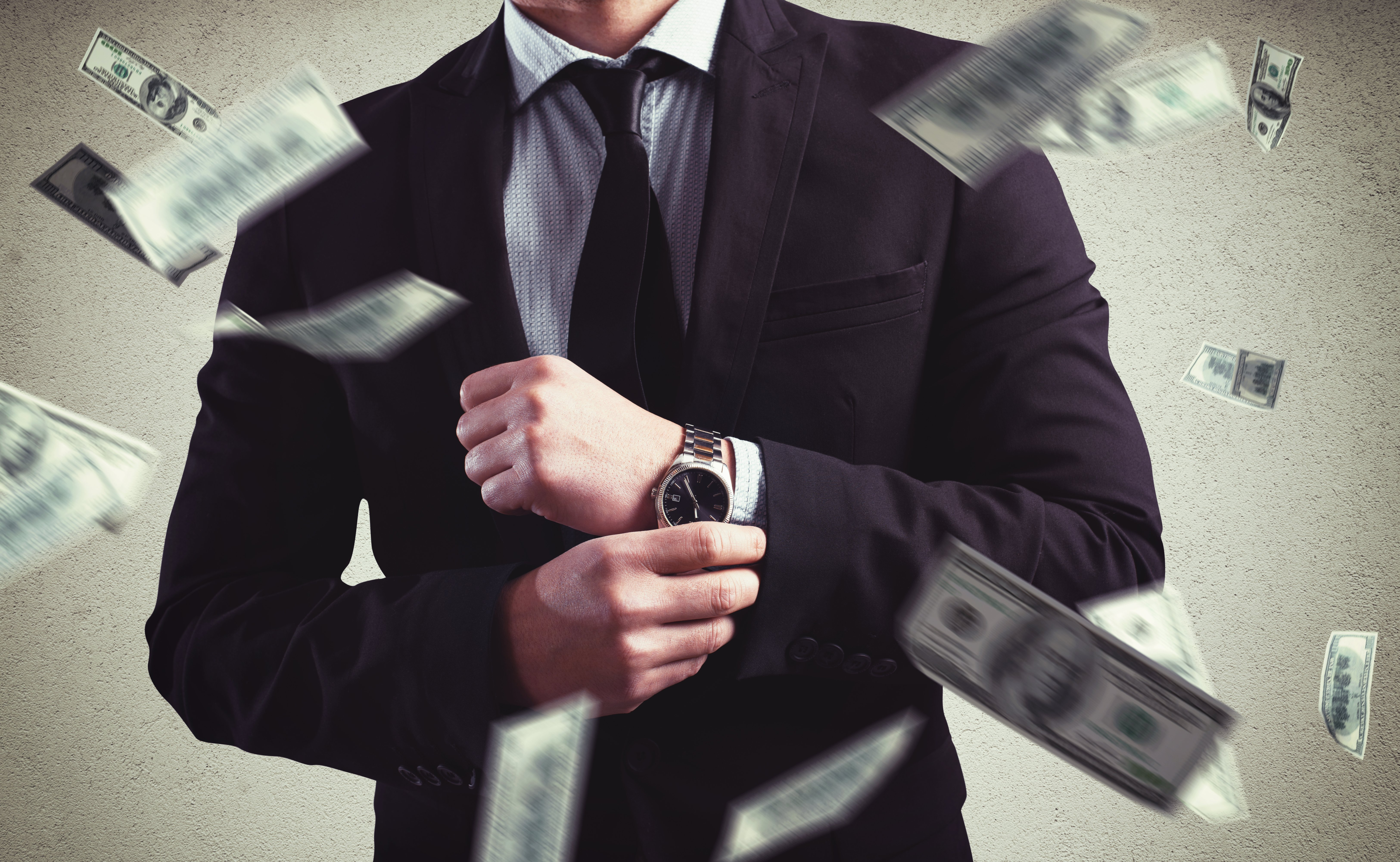 Dollar bills flying around a man who is corporately dressed | Photo: Shutterstock