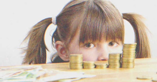 A little girl stands behind a counter with money.   Source: Shutterstock