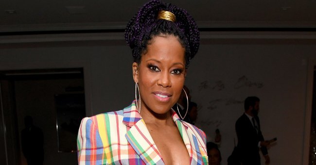 Regina King Takes Fans' Breath Away in Red Versace Dress Posing on a Balcony with Stunning View