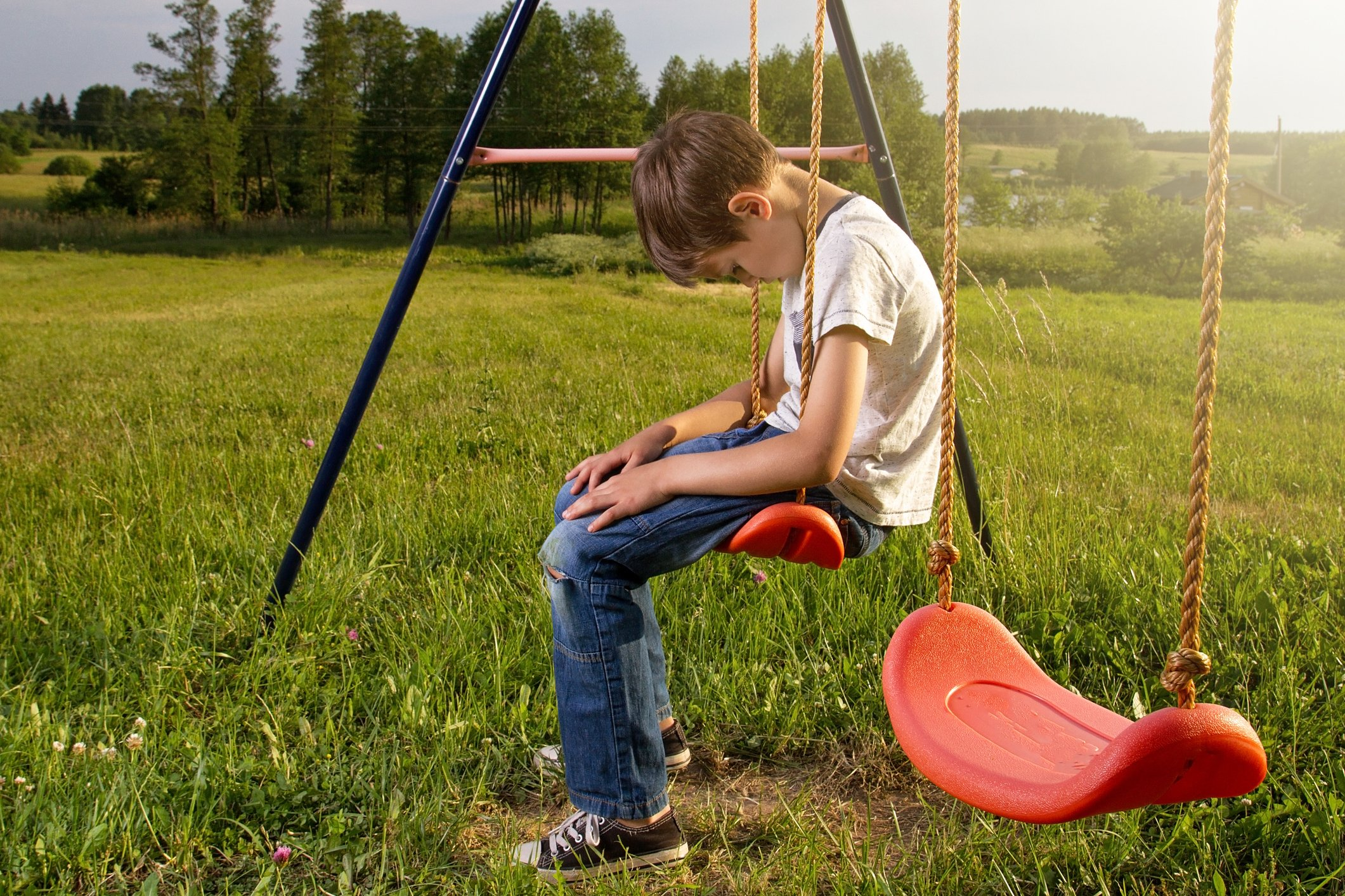 Sad Boy Sitting On Swing At Playground Alone | Photo: Getty Images