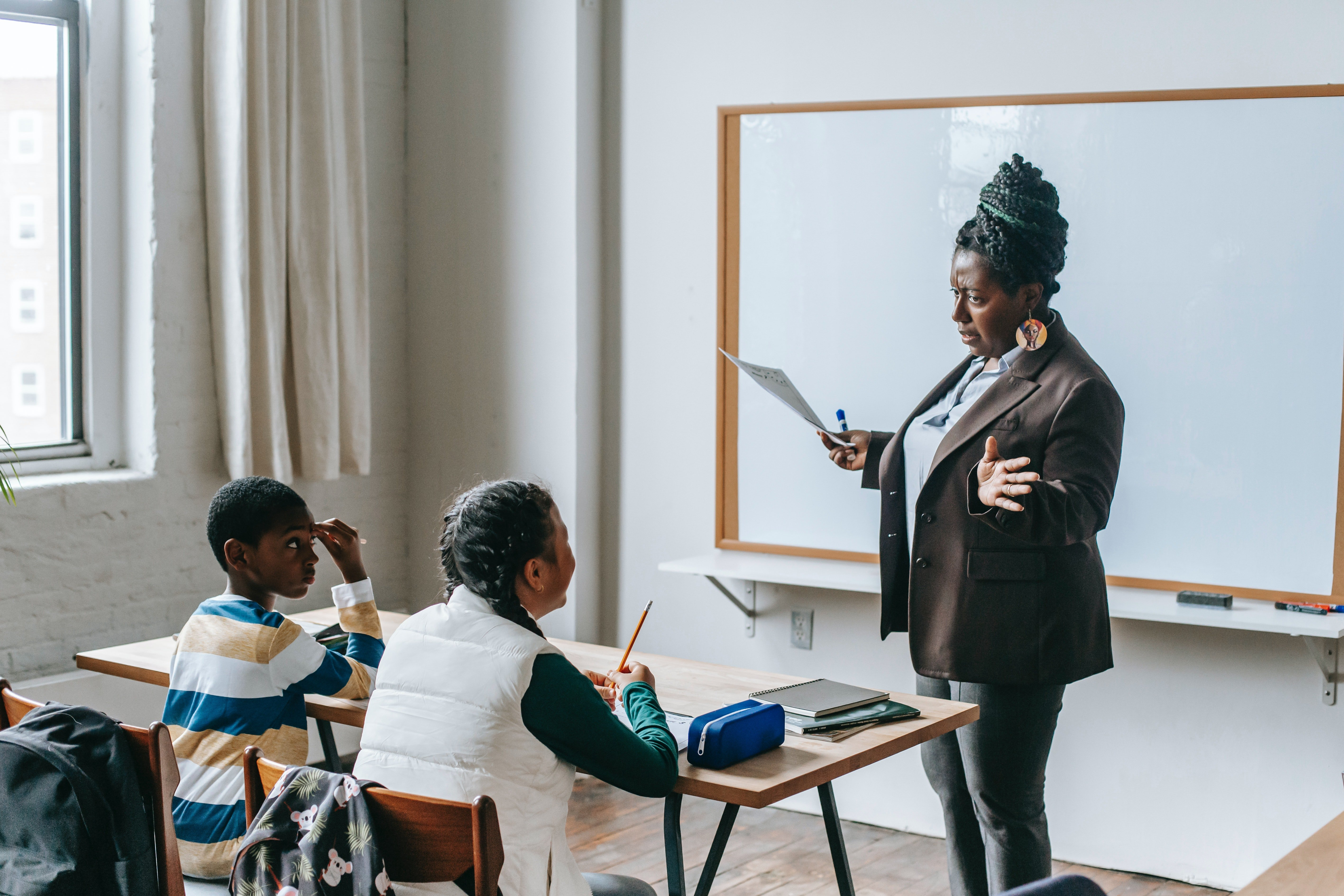 A teacher talking to students in class.   Photo: Pexels/Katerina Holmes