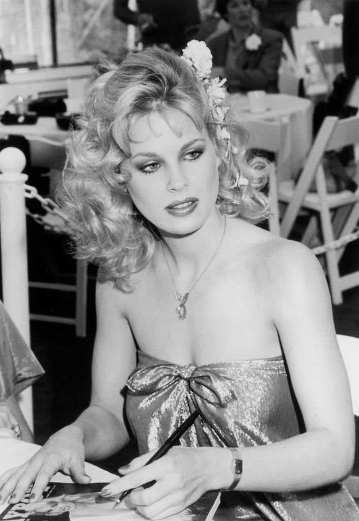 A portrait of Dorothy Stratten holding a pen over a copy of Playboy magazine on May 01, 1980 | Photo: Getty Images
