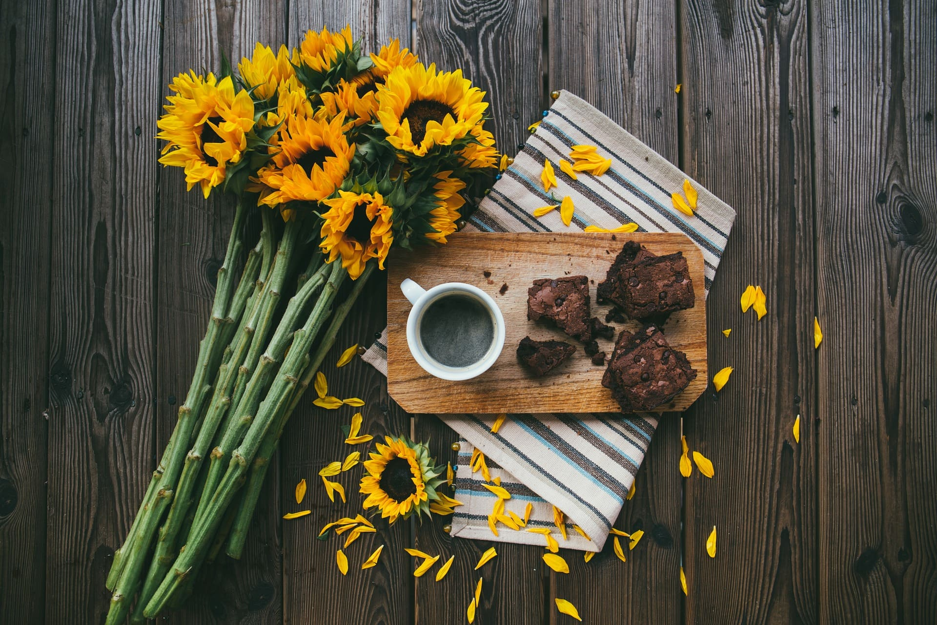 Brownies on a wooden tray with coffee and flowers on the side.  | Source: Pixabay