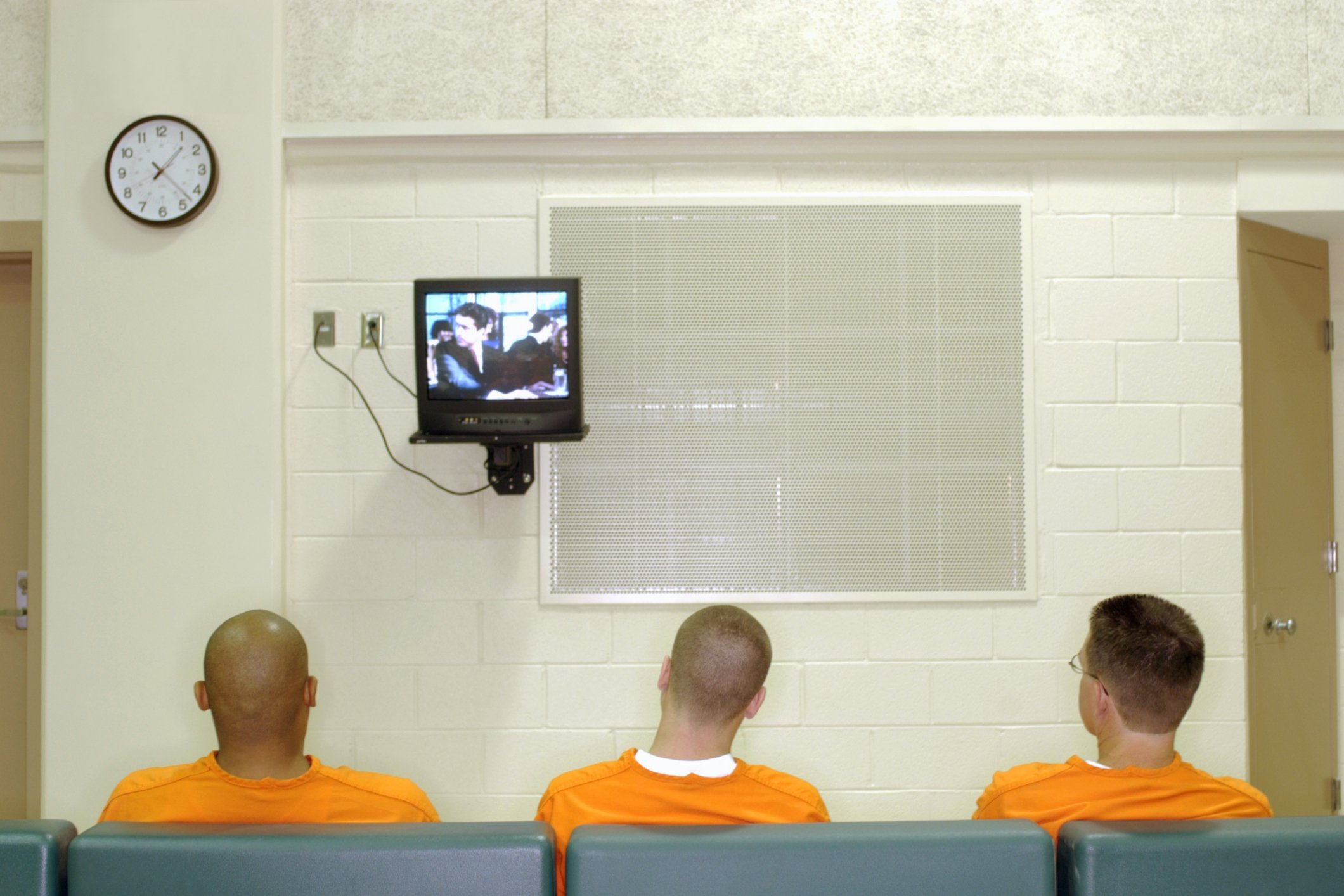 Three inmates seated in prison watching TV. | Photo: Getty Images