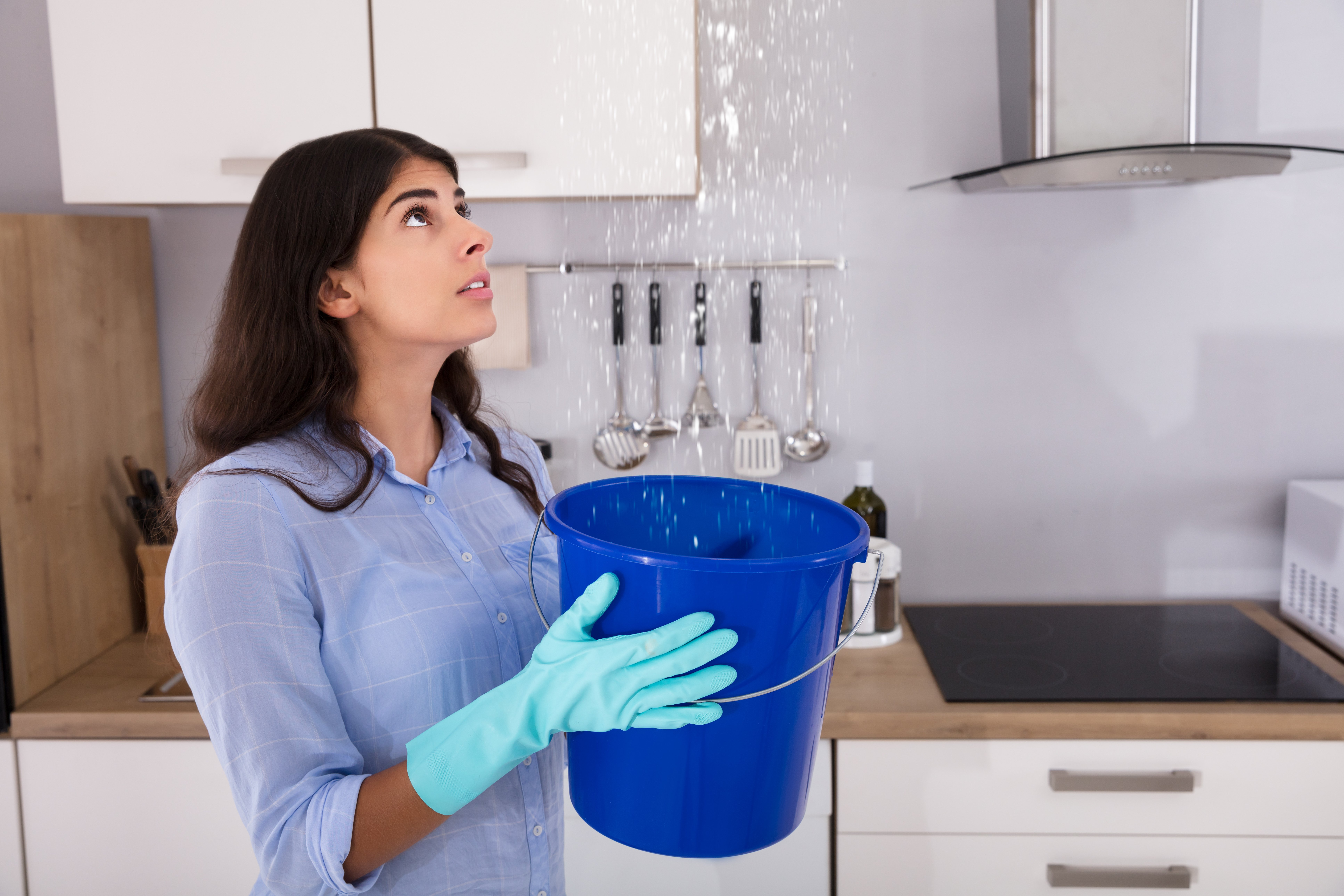Woman standing with a bucket under leaking ceiling. Image credit: Pixabay