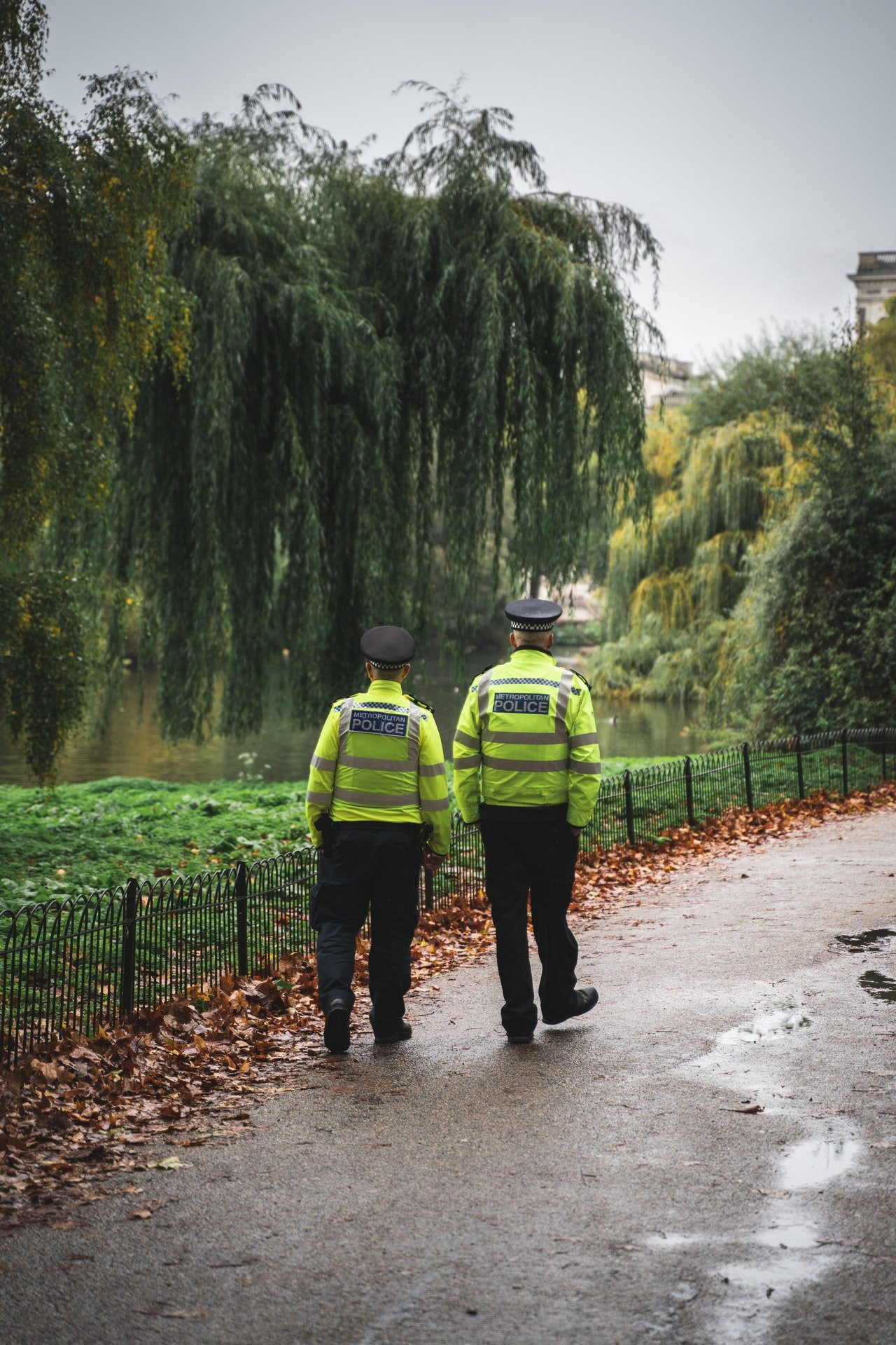 Two police officers walking along the road | Photo: Pexels