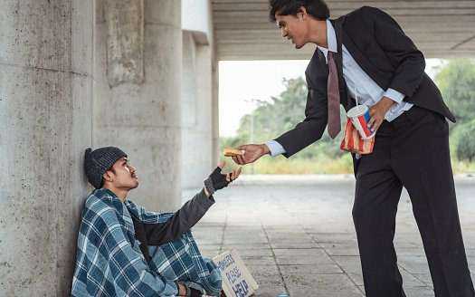 Photo of a kind-hearted businessman giving part of his big meat burger to a homeless man   Photo: Getty Images