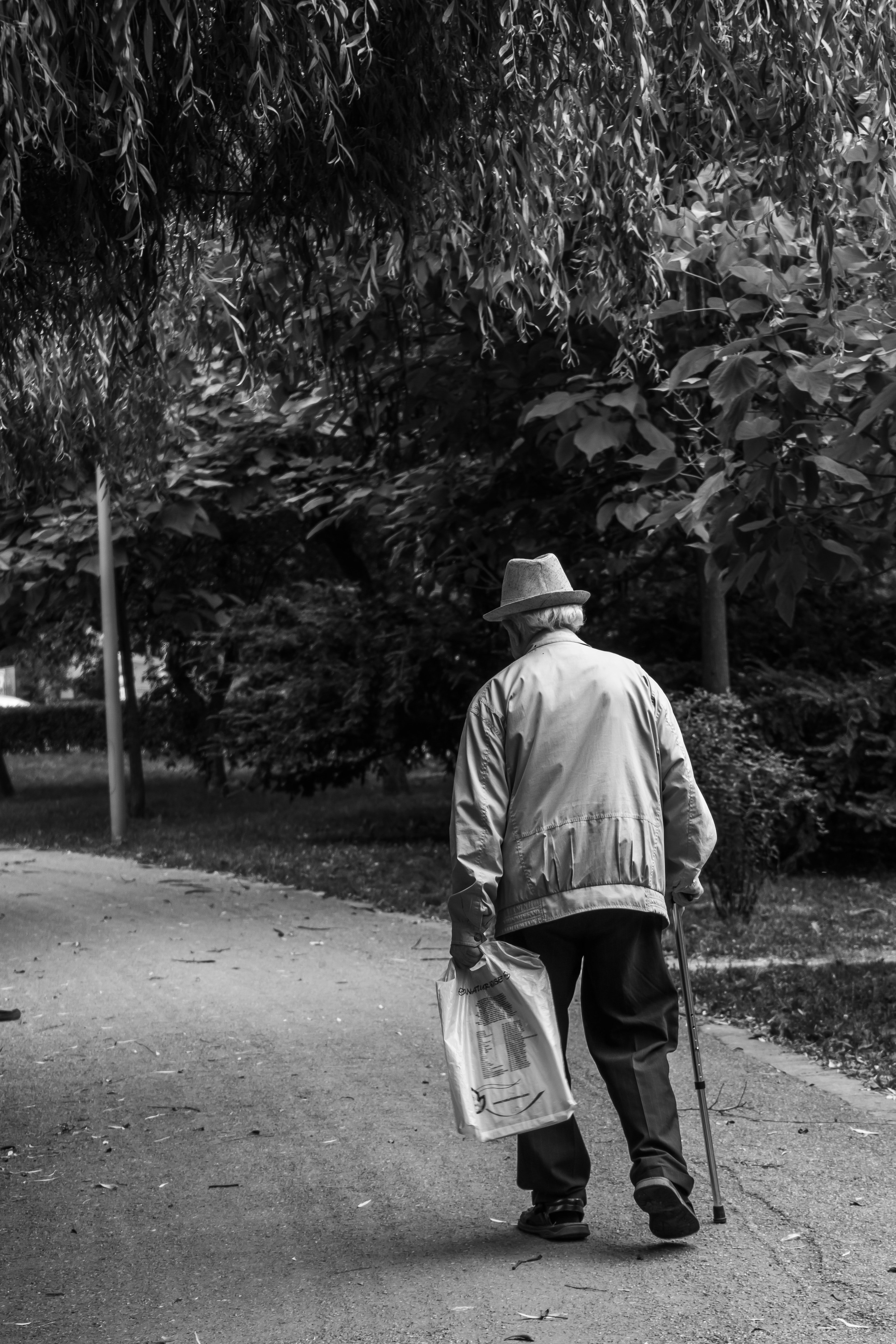 A man walking in the park wearing a hat.   Photo: Pexels