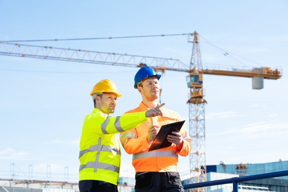 Two male construction workers standing In front of  a crane working at construction site. | Photo: Shutterstock